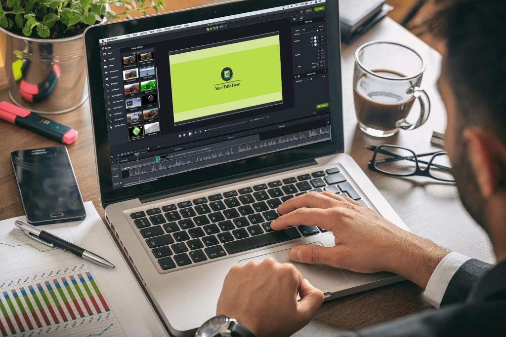 Hands on laptop keyboard with Camtasia 21 on desktop